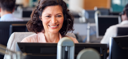 woman happily working on after-sales services on her desktop