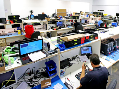 Technicians working to repair small electronics.